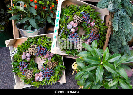 Christmas wreaths with blue berries on plant with red stems and nuts for sale on a garden stall at Borough Market in London England UK  KATHY DEWITT - Stock Photo