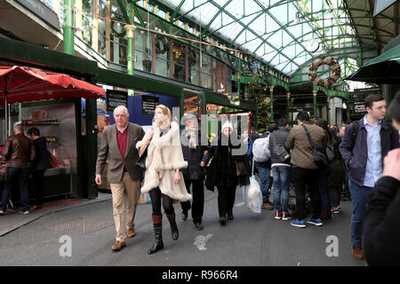 People visiting Borough Market at Christmas time strolling inside past stalls in Southwark South London England UK  KATHY DEWITT - Stock Photo
