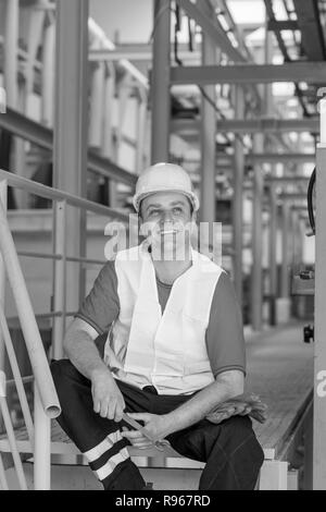 Black and white image of cheerful factory worker resting in a factory and smiling - Stock Photo