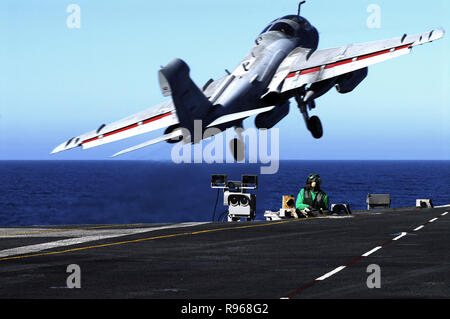 An EA-6B Prowler assigned to the 'Yellowjackets' of Tactical Electronic Warfare Squadron One Three Eight (VAQ-138) takes off from the flight deck as an Aviation Boatswains Mate  prepares to launch the next aircraft aboard the Nimitz- class aircraft carrier USS John C. Stennis (CVN 74). U.S. Navy photo by Mass Communication Specialist 3rd Class Jon Hyde - Stock Photo