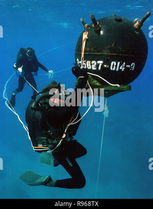 A U.S. Navy diver attaches an inert satchel charge to a training mine, during training exercises in waters off Naval Base Guantanamo Bay, Cuba. DoD photo by Petty Officer 2nd Class Andrew McKaskle, U.S. Navy. - Stock Photo