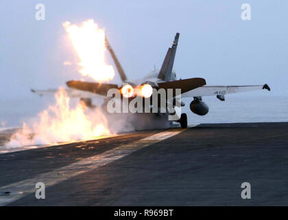 A U.S. Marine Corps F/A-18C Hornet launches with after burners lit from the flight deck of the aircraft carrier USS Abraham Lincoln (CVN 72) operating in the Pacific Ocean on Sept. 15, 2004.  The Hornet is with Marine Fighter Attack Squadron 232.  DoD photo by Petty Officer 2nd class Philip A. McDaniel, U.S. Navy - Stock Photo