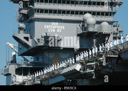 Crewmembers of the USS Enterprise (CVN 65) man the rail as the aircraft carrier departs Naval Station Norfolk, Va. US Navy photo by Jeff Hall - Stock Photo