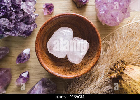 Teak Bowl of Quartz with Amethyst Crystals and Dried Poppy Flower on Wood Table - Stock Photo