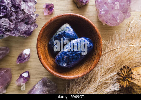 Teak Bowl of Sodalite with Amethyst Crystals and Dried Poppy Flower on Wood Table - Stock Photo