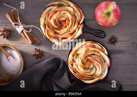 Homemade puff pastry with rose shaped apple slices baked in iron skillets. Hand holding skillet with the pastry with a towel. Top lay on light wood wi - Stock Photo