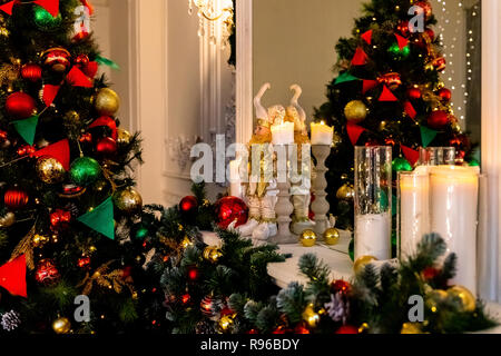 winter decor with candles, spruce branches.Christmas Fireplace, Xmas Lights Decoration, Tree Branches.warm and cozy evening in Christmas room interior design, Xmas tree decorated by lights presents gifts toys.New year holidays - Stock Photo