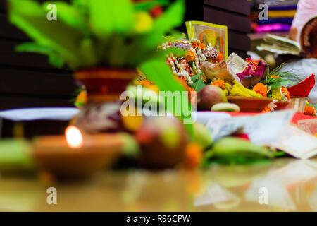 Selective focus. Diwali puja or Laxmi puja set up at home. Oil lamp or diya with crackers, sweet, dry fruits, indian currency, flowers and statue - Stock Photo
