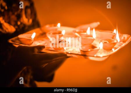 Diwali Festival Lamps in hand, Happy Dipawali, Indian Festival diwali. Female hands holding oil lamp. Celebrating Diwali or Deepawali festival of ligh - Stock Photo