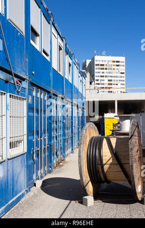 Blue container offices and a big wooden cable reel at a construction site in Budapest, Hungary. Tall block of flats in the background. - Stock Photo