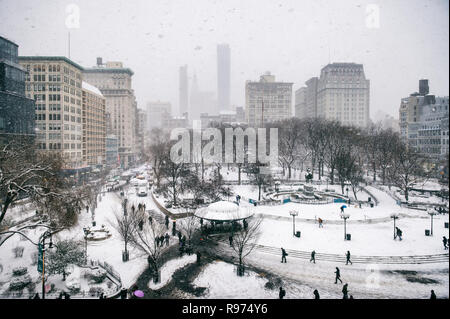 Snowy winter scene with trails left by pedestrians in the snow in Union Square as a blizzard overtakes New York City - Stock Photo