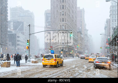 NEW YORK CITY - JANUARY 7, 2017: A winter snowstorm brings pedestrians and traffic to a slow crawl at the Flatiron Building on Fifth Avenue in Midtown - Stock Photo