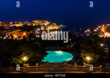View of St. George's Bay seafront lights by night, with a blue luxury swimming pool and boats and yachts anchored. St Julian's (San Giljan), Central Region, Malta. Evening in Paceville district. - Stock Photo