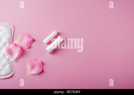 Women's cycle hyhienic pads and tampons on pink background. Copy space. - Stock Photo