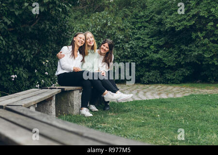 Three young women sitting in a park in Karlskrona, Sweden - Stock Photo