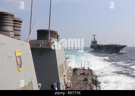 181215-N-N0146-1050 GULF OF OMAN (Dec. 15, 2018) The Arleigh Burke-class guided-missile destroyer USS Decatur (DDG 73), left, pulls away from the aircraft carrier USS John C. Stennis (CVN 74) after completing an underway replenishment. Decatur is deployed to the U.S. 5th Fleet area of operations in support of naval operations to ensure maritime stability and security in the Central Region, connecting the Mediterranean and the Pacific through the western Indian Ocean and three strategic choke points. (U.S. Navy photo by Ensign Xuan Nguyen/Released) - Stock Photo