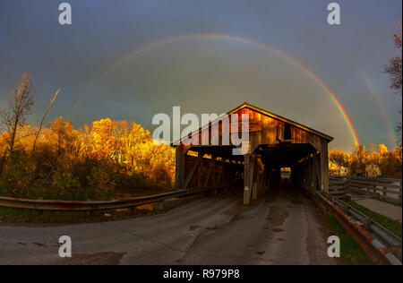 Rainbow over the Pulp Mill Bridge, a covered bridge that spans over Otter Creek in Middlebury, Vermont. - Stock Photo