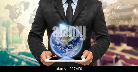 Businessman holding the tablet on Abstract blurred photo of empty computer room with earth and world map,Elements of this image furnished by NASA - Stock Photo