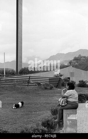 MONTERREY, NL/MEXICO - NOV 2, 2003: A woman watches her daughter as she plays on the grass at the Macroplaza. The Commerce Lighthouse on the backgroun - Stock Photo