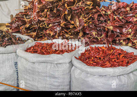 An assortment of dried chilies in white burlap sacks - Stock Photo