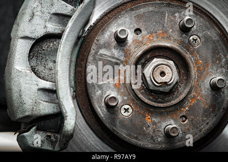 Close-up of the replacement of the old front brake disc, brake caliper and hub nut on a car lifted on a lift with the help of a pneumatic wrench in a  - Stock Photo