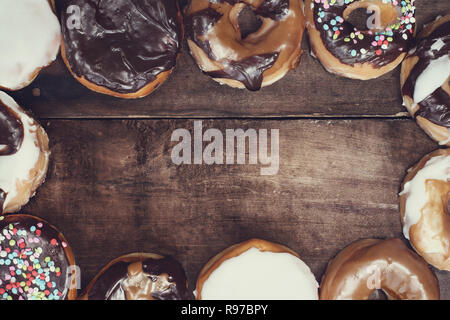 Variety of donuts over a rustic background shot from overhead with copyspace. - Stock Photo