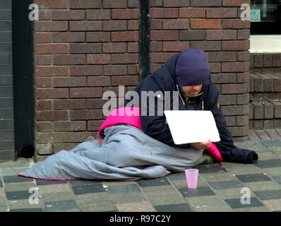 homeless man begging  on street with brick wall  pink cup hiding face holding sign with sleeping bag - Stock Photo
