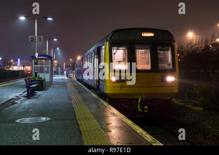 A Arriva Northern rail class 142 pacer train at a wet, dark and misty  Morecambe railway station - Stock Photo