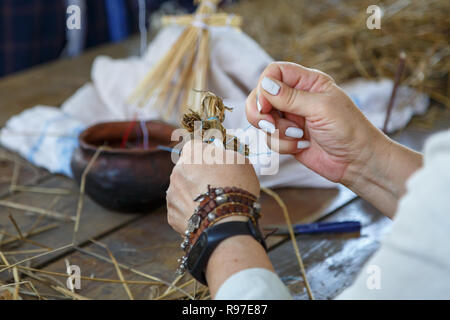 An elderly woman weaves an orthodox cross from straw. Traditional Russian folk art - Stock Photo