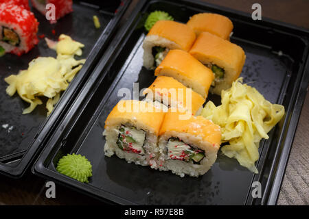 Japanese rolls packed in plastic containers as an example of street food - Stock Photo