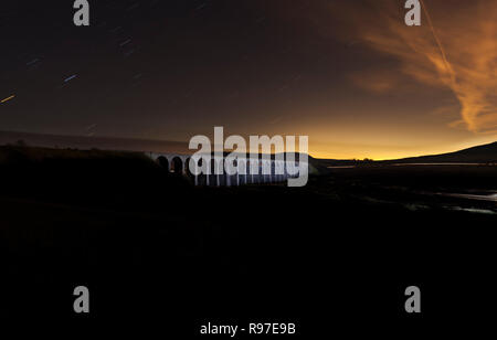 Ribblehead viaduct on the settle to Carlisle railway line at night floodlit by light painting with a torch. Penyghent is behind - Stock Photo
