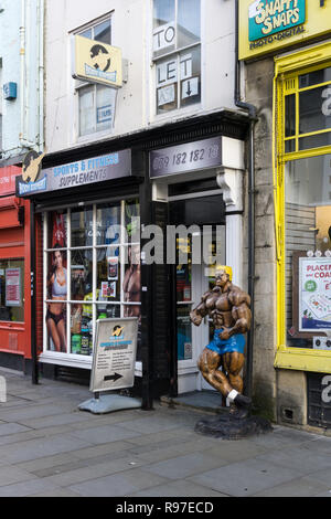 Body Expert, a shop selling sports and fitness supplements, Northampton, UK; with a model of a muscled male bodybuilder by the door.
