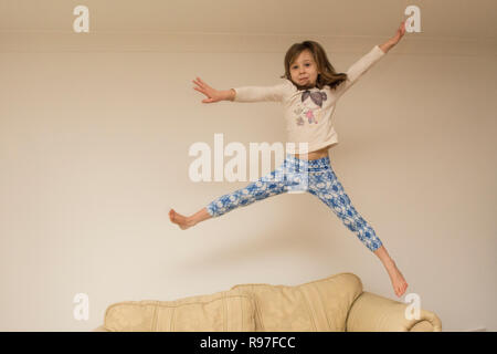 child, girl indoors leaping, jumping on furniture, sofa, being energetic, hyperactive, having fun, six years old, - Stock Photo