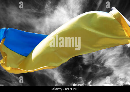 Sunlight Ukrainian flag waving in wind on black and white storm sky - Stock Photo