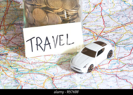 Closeup of coins in a jar with travel sign and a toy car on a map. Abstract of travel expenses. - Stock Photo