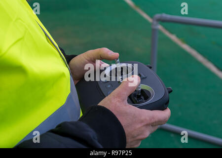 Drone pilot during an exercise wearing a yellow jacket. Pilot pilot aircraft remotely during a simulation. - Stock Photo