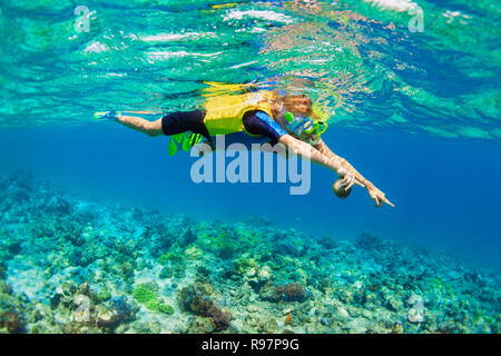 Happy family - mother, kid in snorkeling mask dive underwater, explore tropical coral reef sea pool. Travel active lifestyle, beach swimming adventure