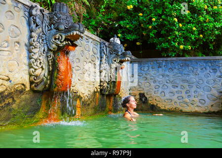 Young woman stand in thermal bath, relaxing under flowing water stream of shower in ancient Balinese hot spring. Popular travel destination on Bali - Stock Photo