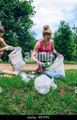 Girls with garbage bag doing plogging - Stock Photo
