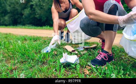 Women picking up trash doing plogging - Stock Photo
