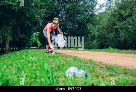 Girl picking up trash doing plogging - Stock Photo