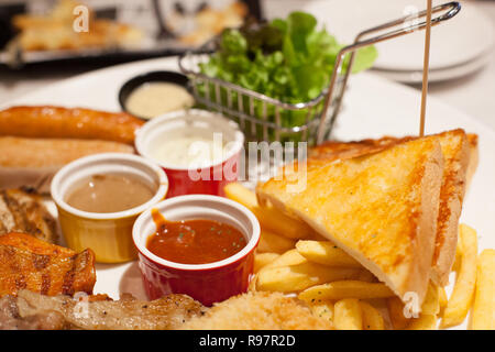Selective Focused Food, French Fries and baked butter bread siding Steaks and Sausages Assortment with varieties of sauces and fresh vegetable in whit - Stock Photo