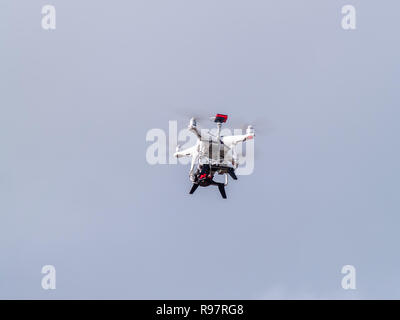 A drone in motion flying in the cloudy sky - Stock Photo