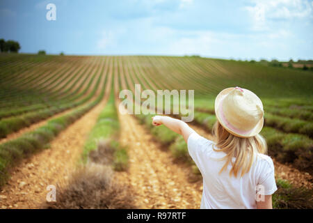 Seen from behind modern child in straw hat in green field in Provence, France pointing at something. stretching to the horizon beautiful green fields. - Stock Photo