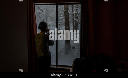 Silhouette of woman talking on phone at window looking out at snow - Stock Photo
