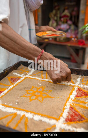 Hindu priest coloring traditional sand art (Rangoli) with religious pattern using colors from natural pigments like sindoor, haldi (turmeric) - Stock Photo