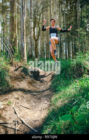 Woman jumping participating in trail race - Stock Photo