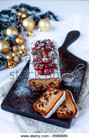 Traditional Christmas Fruit Cake pudding with marzipan and cranberry and rosemary decor on a white table. Festival decoration. View from the top. - Stock Photo