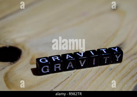Gravity written on wooden blocks. Inspiration and motivation concepts. Cross processed image on Wooden Background - Stock Photo