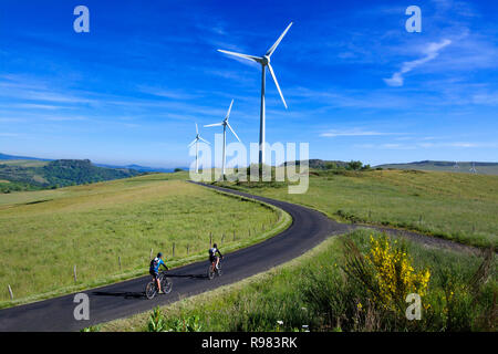 Cyclists on walk in the Cezallier wind farm, Puy de Dome department, Auvergne Rhone Alpes, France - Stock Photo